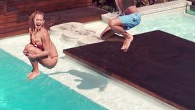 Verbinden Sie das Springen in den Swimmingpool, der enormes Spritzen macht stock footage