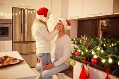 Verbinden Sie das Umarmen in der Küche mit Lichtern für Weihnachten lizenzfreies stockfoto