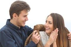 Verbinden Sie das Verlieben in ihn sie mit seiner Jacke bedeckend Stockfotografie