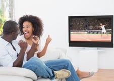 Verbinden Sie das Zujubeln beim Aufpassen des Tennismatches im Fernsehen stockfotografie