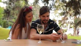 Verbinden Sie Datum, Mann und Frau betrachtet etwas im Smartphone, der dem Tisch sitzt stock video