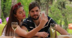 Verbinden Sie Datum, Mann und Frau machen das selfie, das am Tisch sitzt stock video