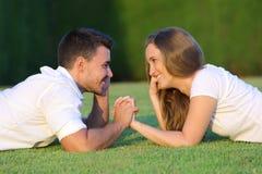 Verbinden Sie den Flirt und das Schauen liegend auf dem Gras lizenzfreie stockfotos