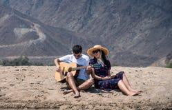 Verbinden Sie den Gesang und das Spielen der Gitarre, den Strand zu kaufen stockfotografie
