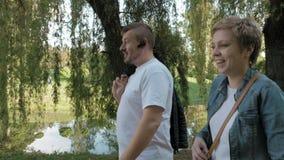 Verbinden Sie den Mann und Frau, die in den Park im Sommer gehen stock video