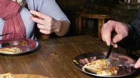 Verbinden Sie den Mann und Frau, die Pizza in einem Café essen stock footage