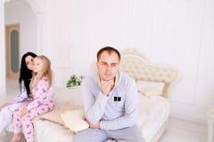 Verbinden Sie den Streit und Kinderumkippen und Bett im weißen Innenraum sitzen Stockfotografie