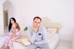 Verbinden Sie den Streit und Kinderumkippen und Bett im weißen Innenraum sitzen Stockfoto
