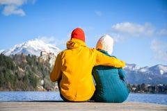 Verbinden Sie in der Liebe, die zusammen mit den bunten Stoffen umarmt, die auf einem hölzernen Pier auf einer Wintertagesansicht stockfotografie