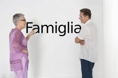 Verbinden Sie die Diskussion von Familienfragen gegen weiße Wand mit italienischem Text Famiglia Stockfotografie