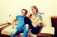 Verbinden Sie die Entspannung auf dem Sofa, die hörende Musikfrau des Mannes, die ihn umarmt lizenzfreies stockfoto