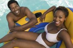 Verbinden Sie die Entspannung im Pool auf Schlauchboot erhöhtem Ansichtporträt. Stockfotos