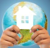 Verbinden Sie die Hände, die grünes Haus über Erdkugel halten Lizenzfreie Stockfotografie