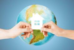 Verbinden Sie die Hände, die grünes Haus über Erdkugel halten Lizenzfreie Stockbilder