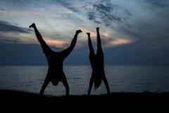 Verbinden Sie die Herstellung des Handstandes am Strand während des Sonnenuntergangs lizenzfreies stockbild