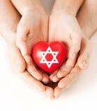 Verbinden Sie die Hände, die Herz mit Davidsstern halten Stockbilder