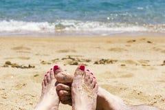 Verbinden Sie Füße auf dem Strand, Türkismeer, Liebeskonzept Stockbilder