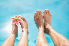 Verbinden Sie Füße gegen Swimmingpool an einem sonnigen Tag Lizenzfreie Stockbilder
