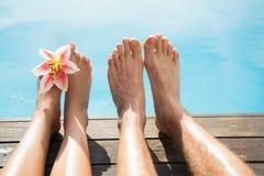 Verbinden Sie Füße gegen Swimmingpool an einem sonnigen Tag Stockfoto