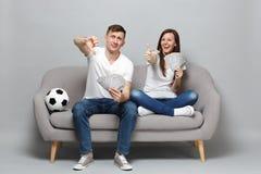 Verbinden Sie Frauenmann, den Fußballfane oben dem Stützlieblingsteam zujubeln, das Fan des Geldes im Dollarbanknotenbargeld hält lizenzfreies stockfoto
