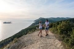 Verbinden Sie glücklichen Mann und die Frau, die auf eine Landstraße in den Bergen mit Meerblick geht Front View Lizenzfreie Stockbilder