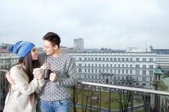 Verbinden Sie glückliches in der Liebe, die nahe Geländer mit Tassen Tee oder Co umarmt stockbilder