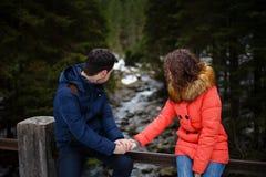 Verbinden Sie Händchenhalten auf einer Brücke und das Betrachten von einem Fluss Stockbilder