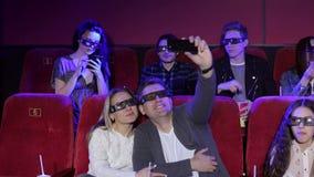 Verbinden Sie im Kino in den Gläsern 3D macht selfie, bevor Sie den Film aufpassen stock video footage