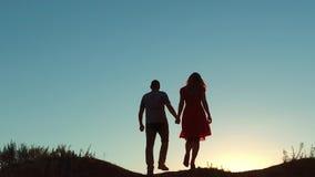 Verbinden Sie Kussliebes-Holdinghand des Schattenbildes gehende in Richtung zum Sonnenfreien am drastischem Himmelhintergrund und stock footage
