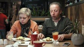Verbinden Sie Mann, den Frau Gespräche isst und einen neuen Teller versucht stock video