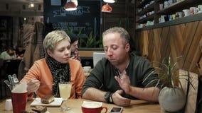 Verbinden Sie Mann, den Frau Gespräche isst und einen neuen Teller versucht stock video footage