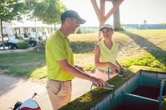 Verbinden Sie oder zwei beste Freunde, die ihre Vereine in einem Club des professionellen Golfs säubern Lizenzfreie Stockfotos
