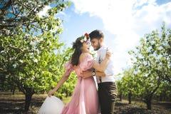 Verbinden Sie Porträt eines Mädchens und des Kerls, die nach einem Hochzeitskleid, einem rosa Kleiderfliegen mit einem Kranz von  Lizenzfreies Stockfoto