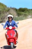 Verbinden Sie reitenen roten Roller auf einer sandigen Straße Lizenzfreie Stockfotografie