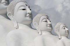 Verbinden Sie ruhige weiße Buddha-Statuen, die wohle Ausrichtung sitzen und wunderbaren attraktiven Spiegel verzieren stockfoto