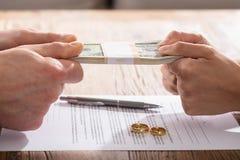 Verbinden Sie ` s Hand, die Währung über der Scheidungs-Vereinbarung hält lizenzfreies stockbild