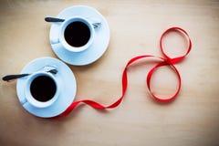 Verbinden Sie Schalen mit dem Kaffee, verziert durch Band auf Holztisch Lizenzfreies Stockfoto