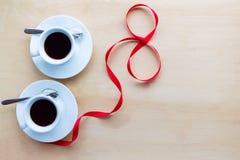Verbinden Sie Schalen mit dem Kaffee, verziert durch Band auf Holztisch Lizenzfreie Stockbilder