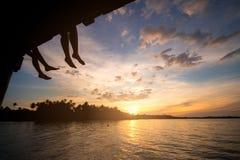 Verbinden Sie Schattenbild und aufpassende Sonne bei Sonnenuntergang auf dem Strand in Thailand lizenzfreie stockfotos