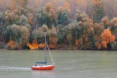 Verbinden Sie Segeln auf kleiner Yacht im Fluss auf schönem Herbst d Stockbild