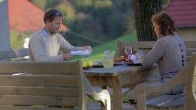 Verbinden Sie Sitzplätze hinter der Tabelle, die sich draußen für Mahlzeit vorbereitet stock video footage