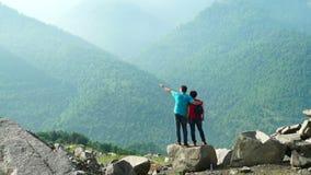 Verbinden Sie Stellung auf dem großen Stein in den nebeligen Bergen stock video footage