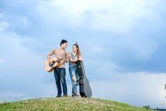 Verbinden Sie Stellung auf dem Hügel und der Akustikgitarre des Spiels Stockbilder