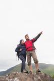 Verbinden Sie Stellung auf einem Felsen, der oben den Bergen betrachtet stockfoto