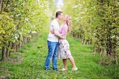 Verbinden Sie Stellung im Obstgarten und auf Lippen mit geschlossenen Augen küssen Stockbilder