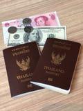 Verbinden Sie thailändischen Pass mit US-Dollar und chinesischem Geld auf der hölzernen Tabelle für Reise lizenzfreies stockbild