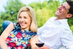 Verbinden Sie trinkenden Rotwein auf Gras des Parks lizenzfreie stockfotos