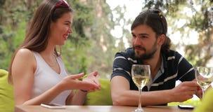 Verbinden Sie Unterhaltungssitzen des Datums, des Mannes und der Frau am Tisch stock video footage