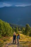 Verbinden Sie Wanderer mit dem Rucksackhändchenhalten und in die Berge gehen Stockbild