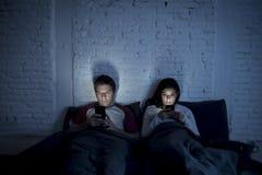 Verbinden Sie zu Hause im Bett spät nachts unter Verwendung des Handys im Verhältnis-Kommunikations-Fehler lizenzfreies stockbild